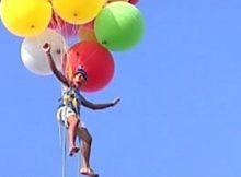 Studente in volo con palloncini